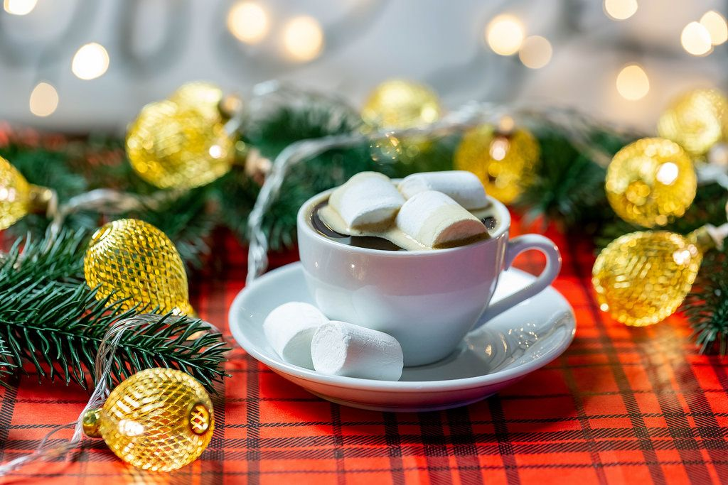 Eine Tasse heiße Schokolade mit Marshmallows umgeben von Weihnachtsdeko