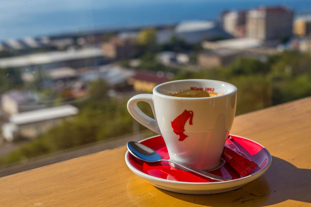 Eine Tasse Julius Meinl Kaffee einem Geländer - Bokeh