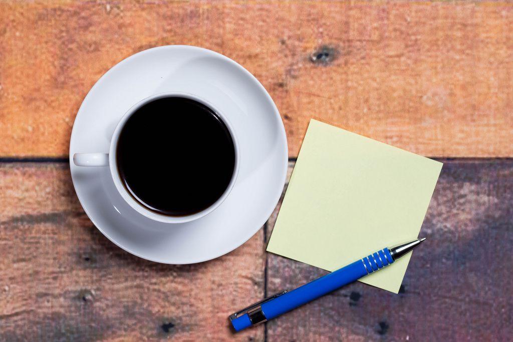Eine Tasse Kaffee mit einer Sticky Note und einem Stift - Aufsicht
