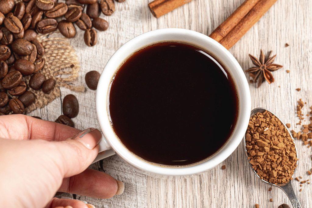 Eine Tasse Kaffee mit Zimt, Anis und Kaffeebohnen auf einem Holzhintergrund Top-view