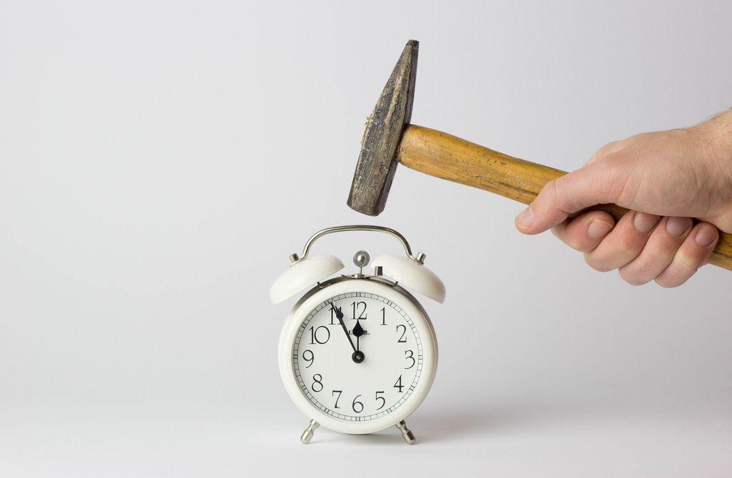 Eine Uhr mit einem Hammer kaputt machen