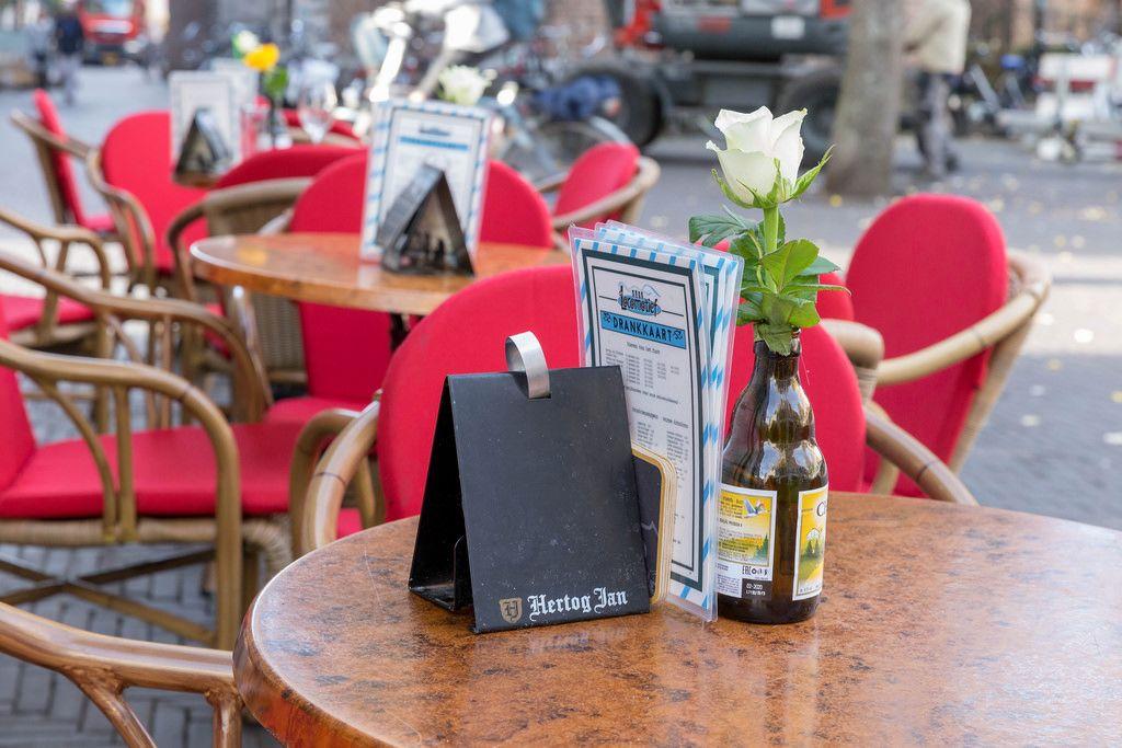 Eine weiße Rose in einer leeren Flasche Bier auf dem Tisch in einem Biergarten