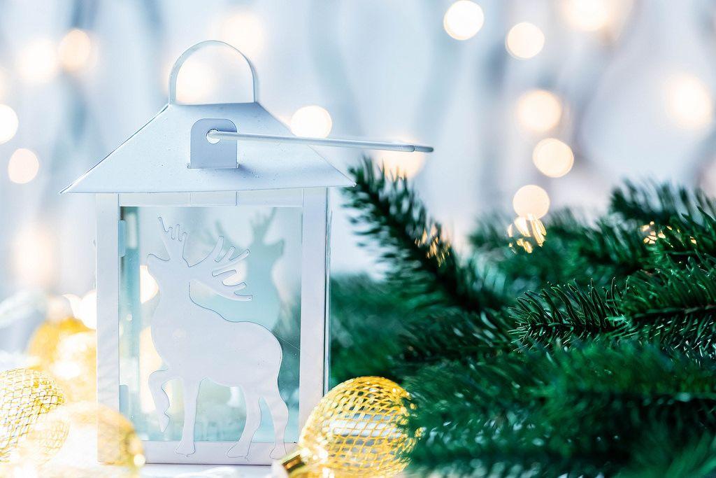 Eine weiße Weihnachtslanterne mit einem Hirsch mit Tannenzweigen und Lichtern im Hintergrund
