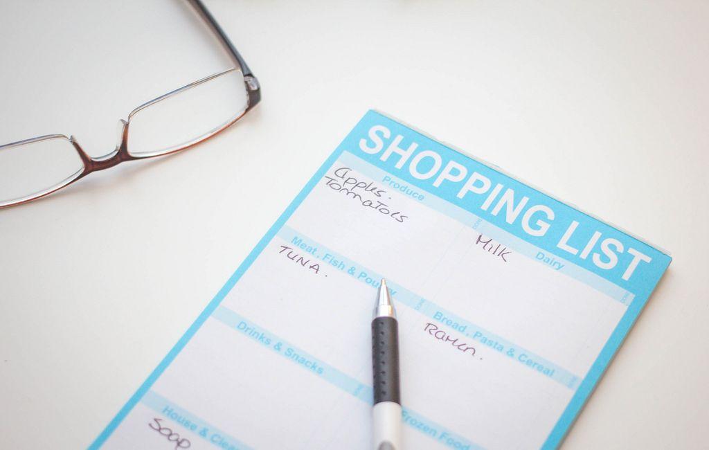 Einkaufsliste mit Kategorien - mit Stift und Brille auf weißem Tisch
