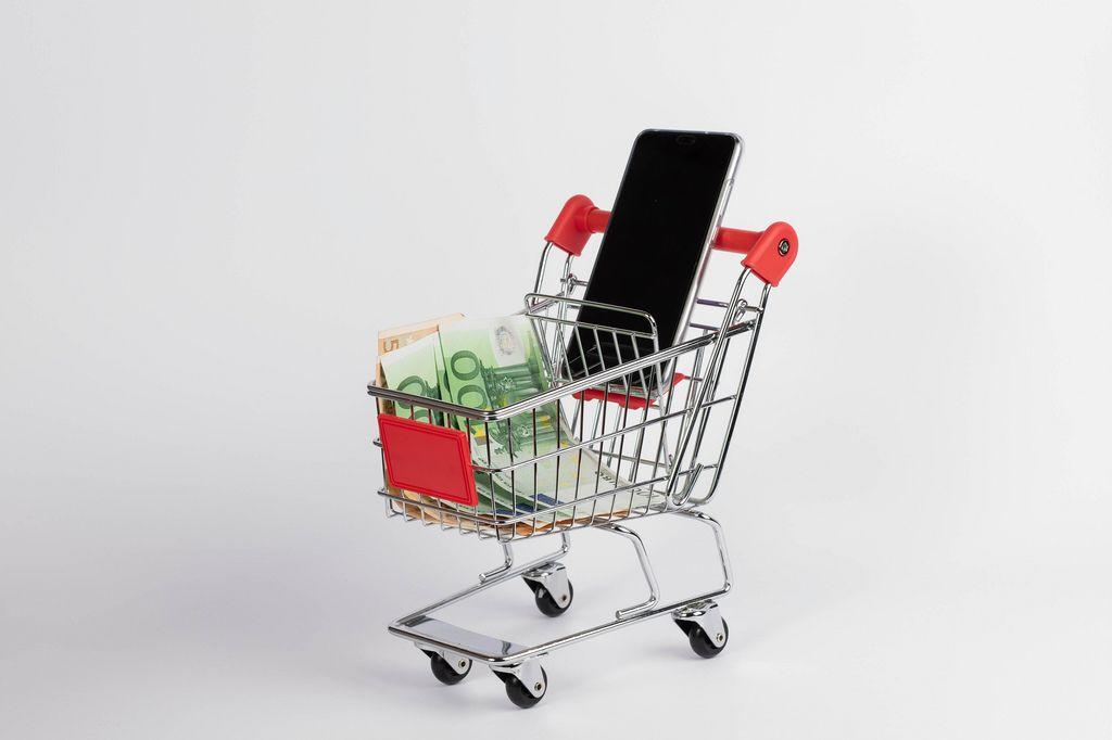 Einkaufswagen gefüllt mit Smartphone und Euro-Banknoten vor weißem Hintergrund