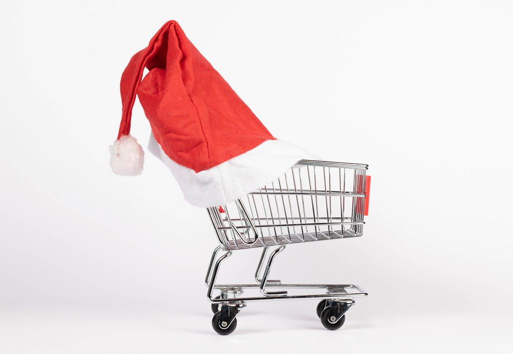 Einkaufswagen trägt Weihnachtsmütze und symbolisiert Weihnachtseinkäufe