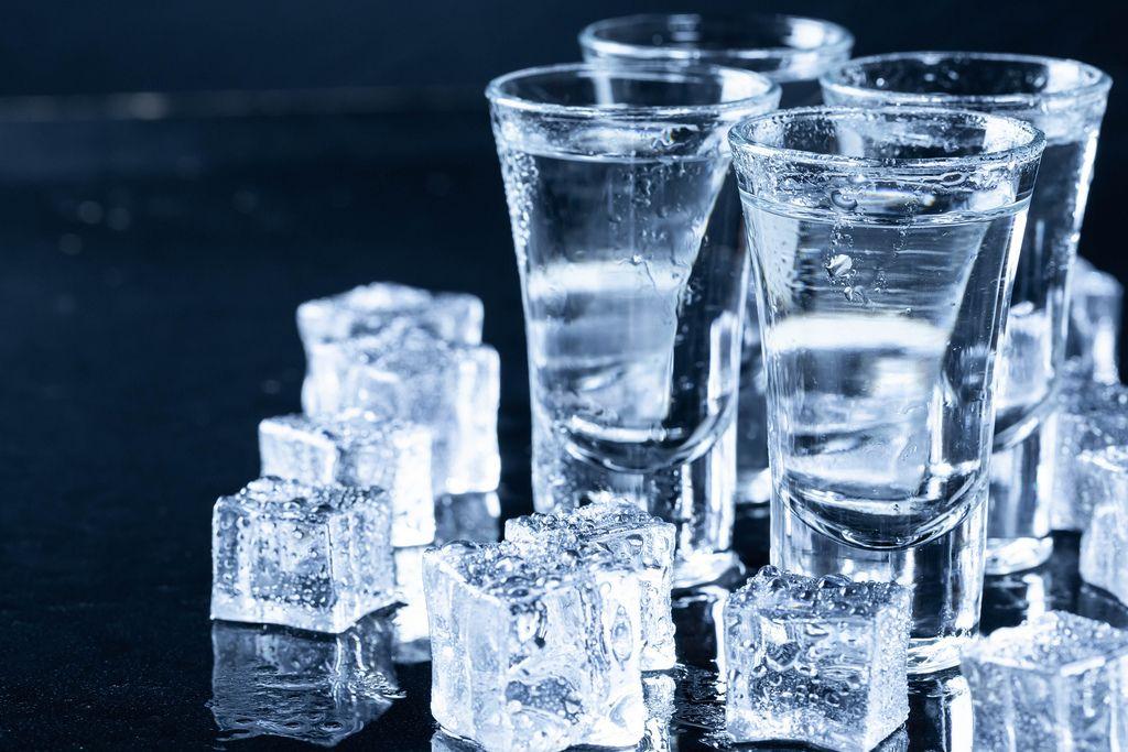 Eiswürfel liegen neben Shotgläsern mit Wodka auf schwarzem Tisch