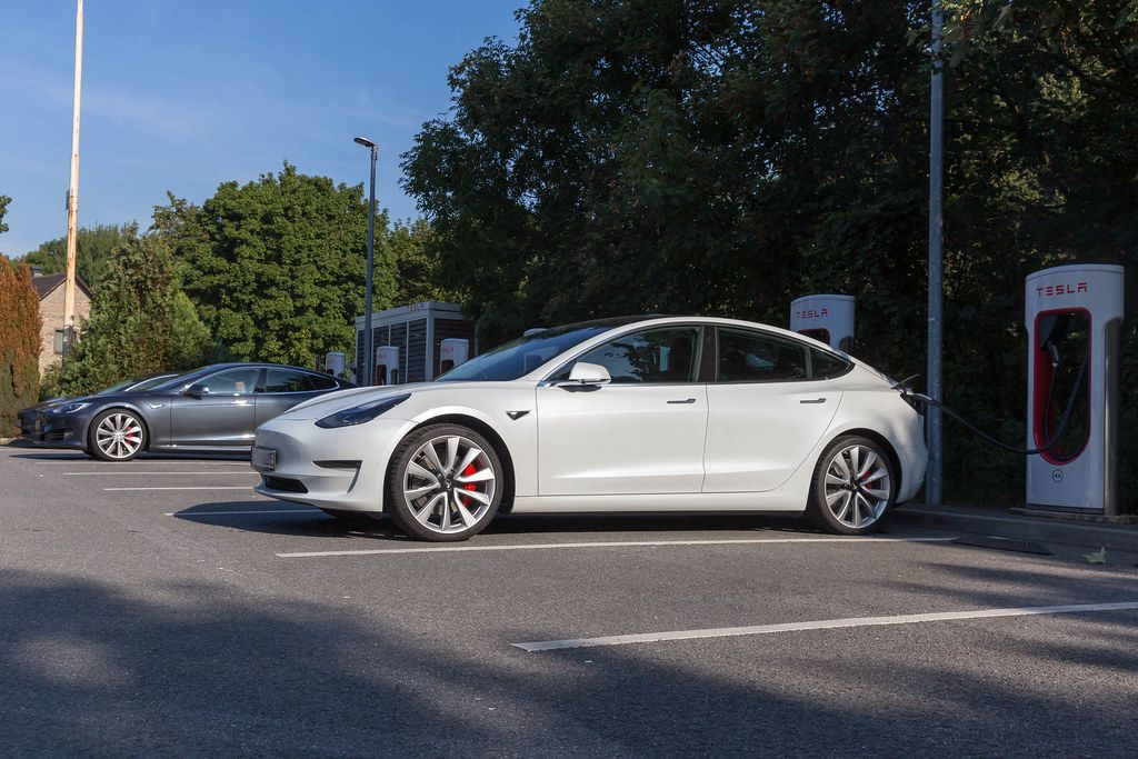 Electric car Tesla Model 3 parks in the shade, in front of Supercharger stations