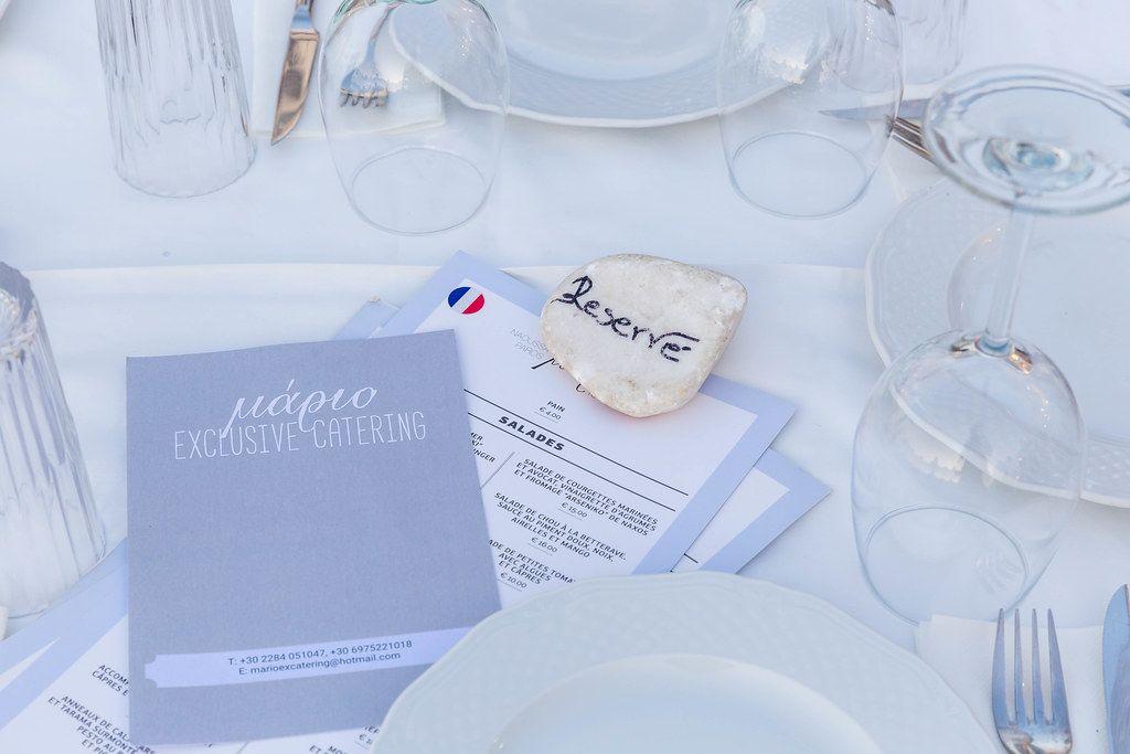 """Elegant gedeckter, mediterraner Tisch mit Speisekarte und Stein mit Aufschrift """"RESERVE"""""""