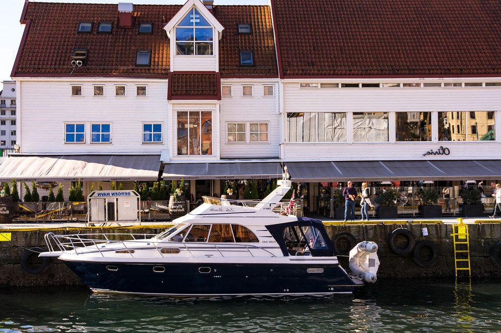 Elegant yacht in the harbor of Bergen, Norway with restaurant Olivia Zachariasbryggen behind (Flip 2019)