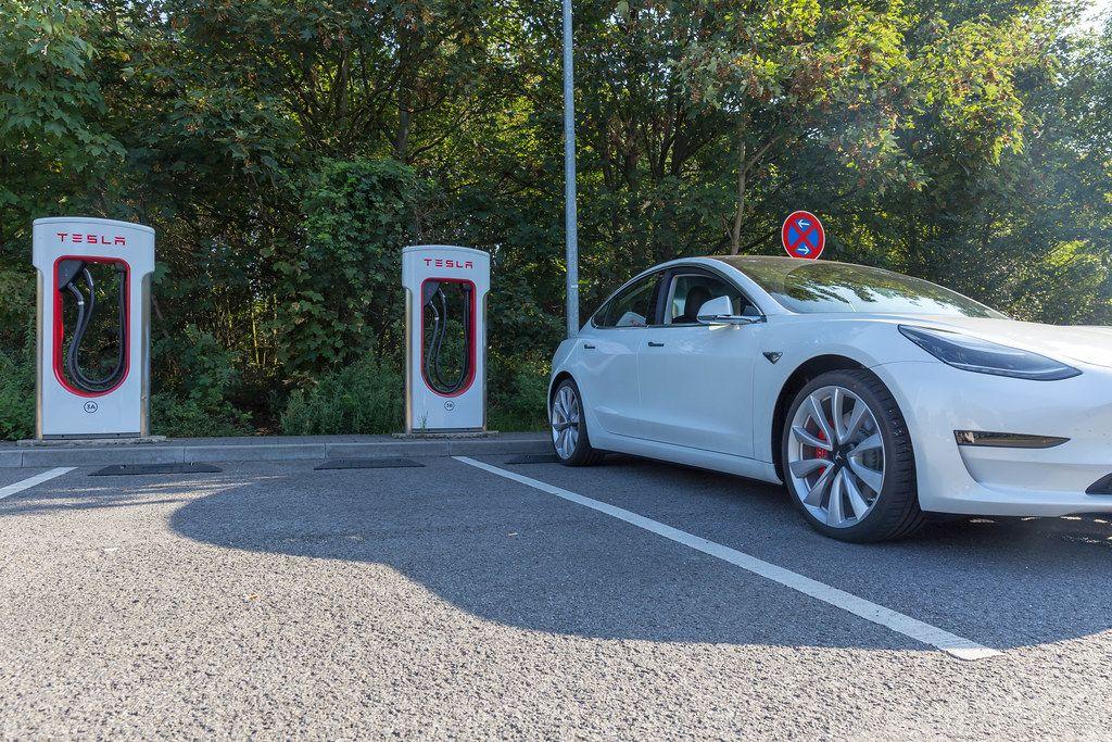 Elektroauto von Tesla parkt im Schatten vor den Supercharger-Ladesäulen