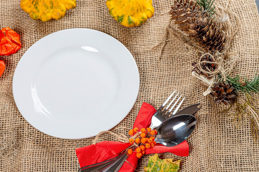 Empty plate with Cutlery on burlap with autumn background (Flip 2019)