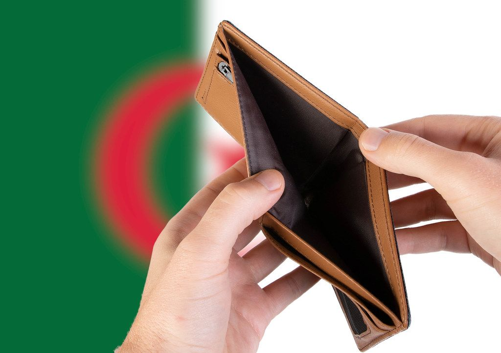 Empty Wallet with Flag of Algeria. Recession and Financial Crisis to come with more debt and federal budget deficit?