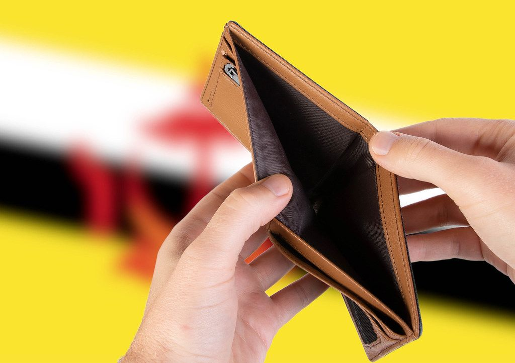 Empty Wallet with Flag of Brunei. Recession and Financial Crisis to come with more debt and federal budget deficit?