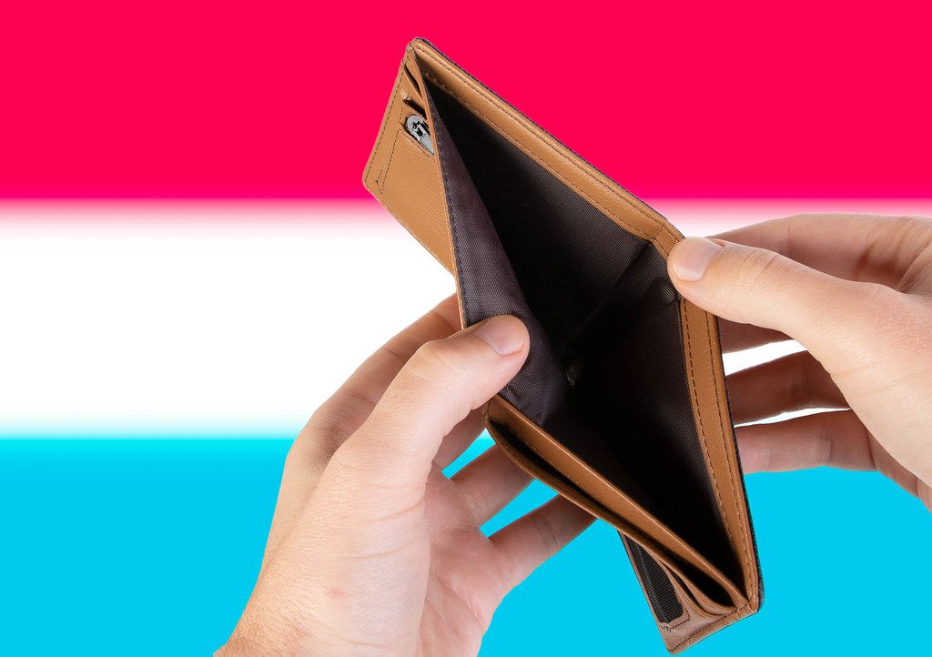 Empty Wallet with Flag of Luxembourg. Recession and Financial Crisis to come with more debt and federal budget deficit?