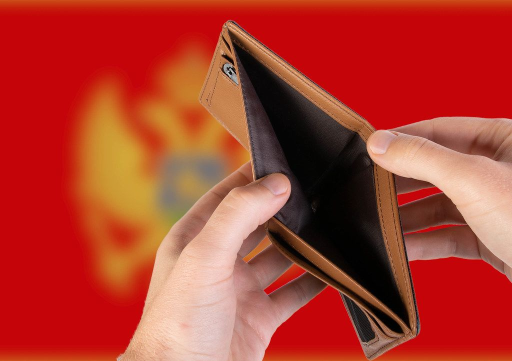 Empty Wallet with Flag of Montenegro. Recession and Financial Crisis to come with more debt and federal budget deficit?