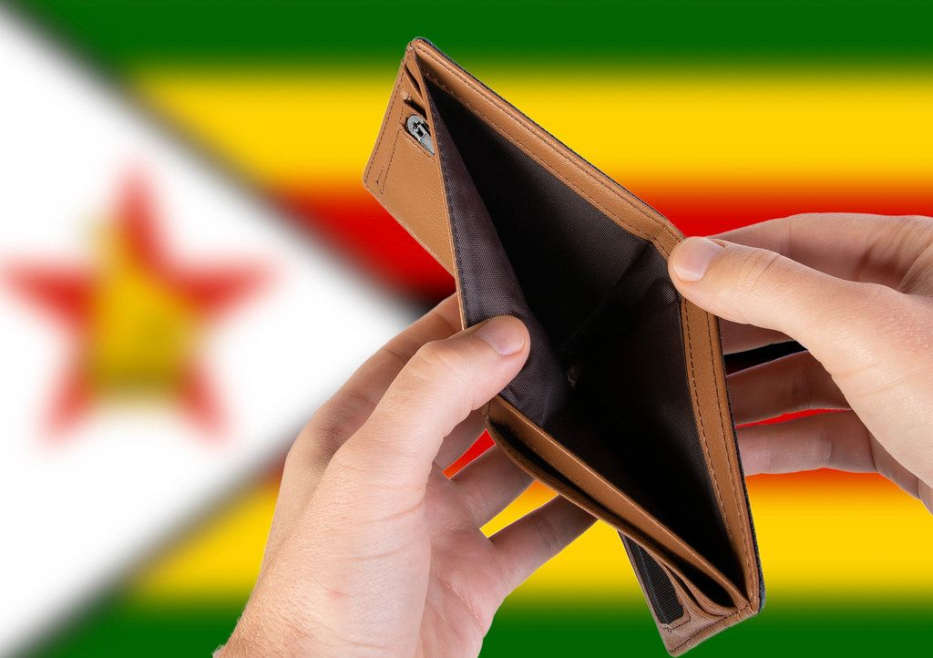 Empty Wallet with Flag of Zimbabwe. Recession and Financial Crisis to come with more debt and federal budget deficit?