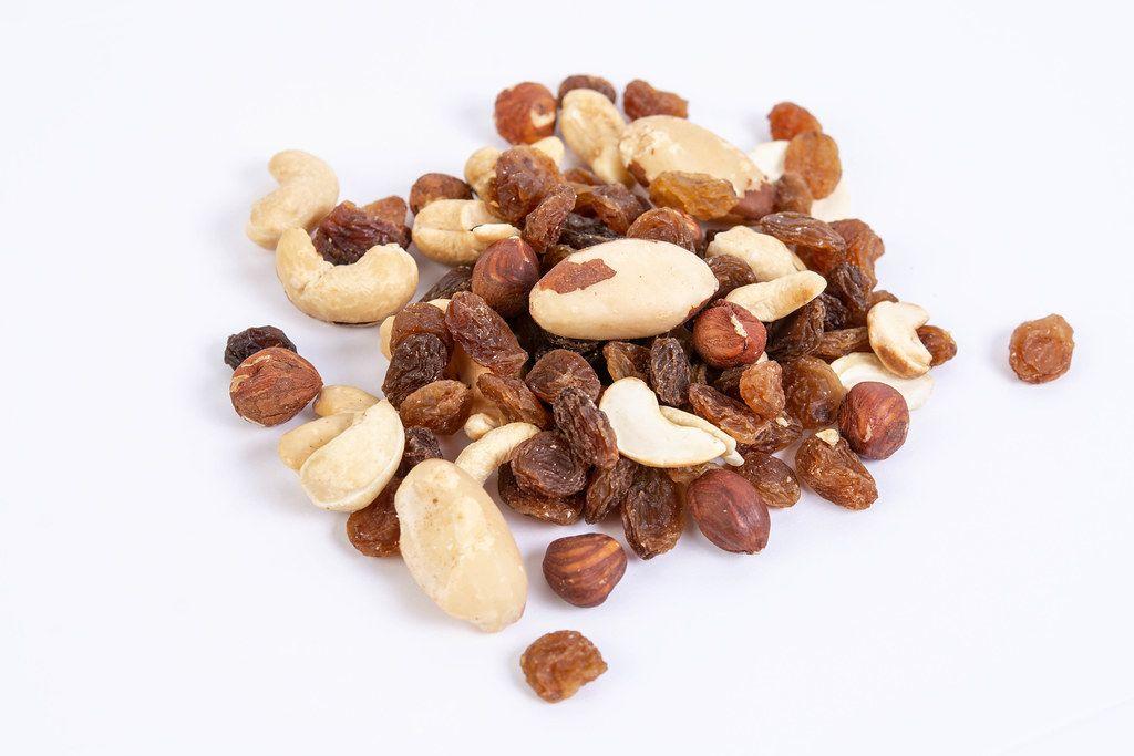 Energy mix with raisins hazelnuts cashew and brazilian nuts above white background