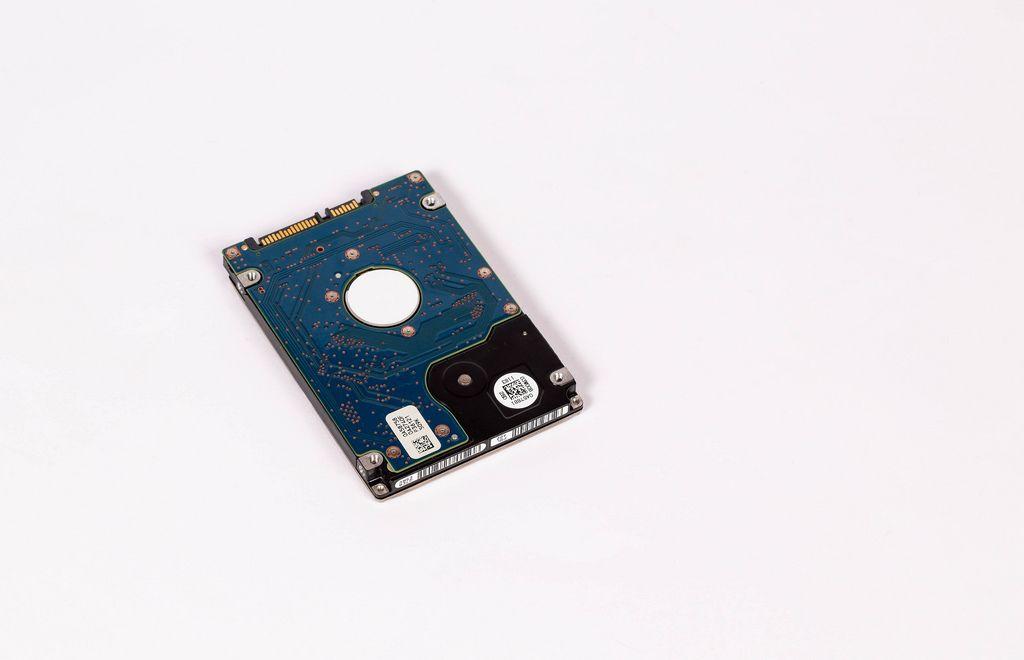 Entfernte Harddisk (Festplatte aus einem Computer oder Laptop) vor weißem Hintergrund