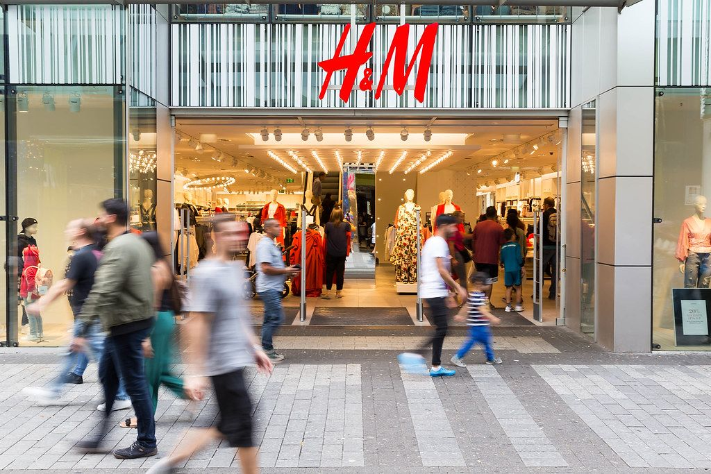 Entrance and Store Front of H&M Shop with Pedestrians walking past