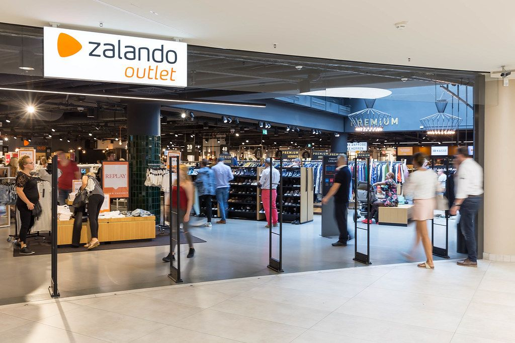 Entrance of a Zalando Outlet Store with People walking around