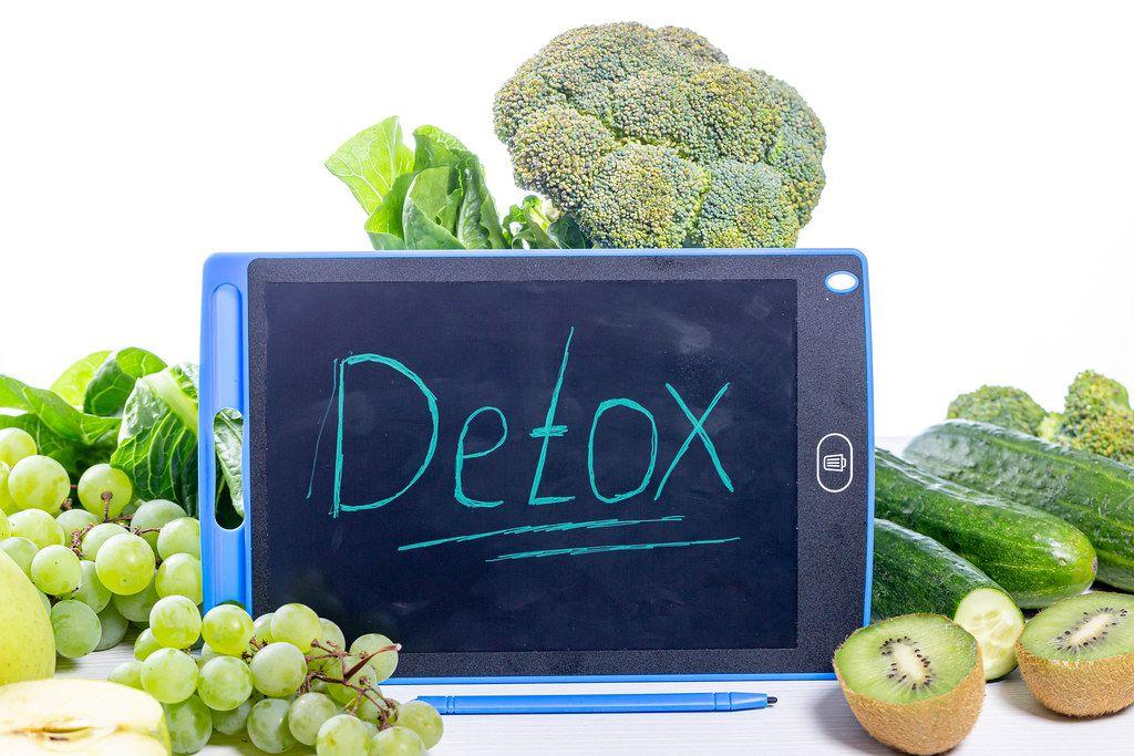 Entschlackung: Detox auf einer Tafel geschrieben, umgeben von grünen Lebensmitteln, Trauben, Gemüse und Salat