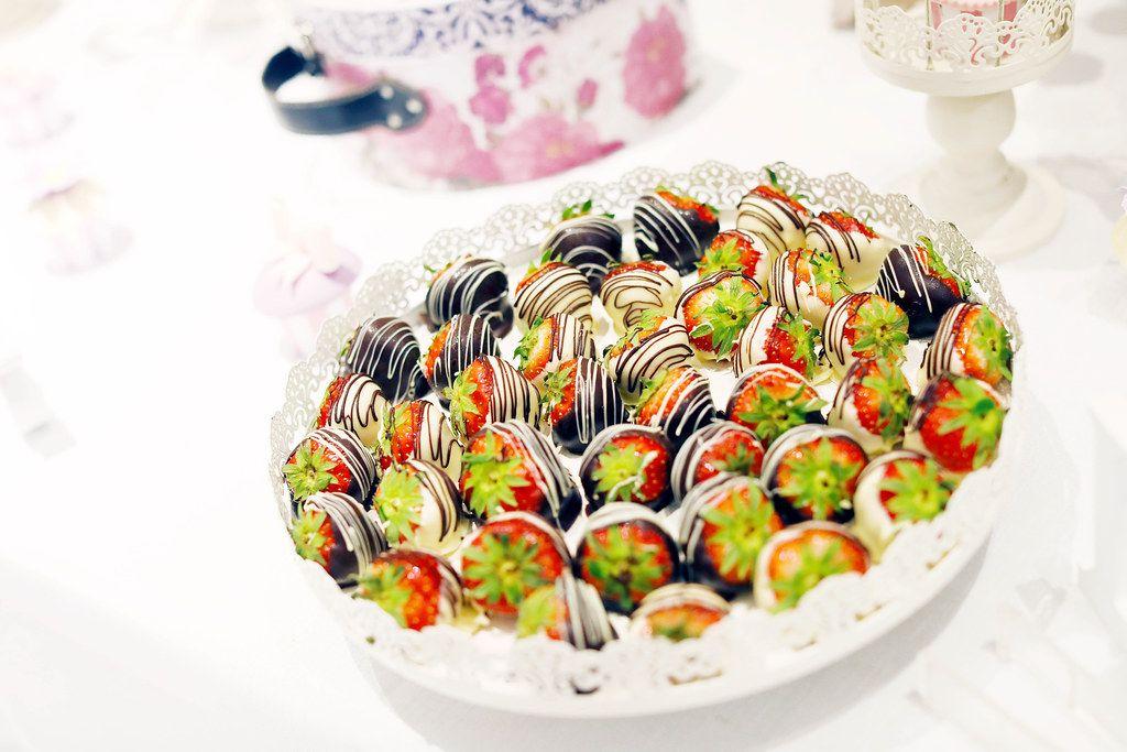 Erdbeeren in dekorativer weißer und dunkler Schokoladenhülle