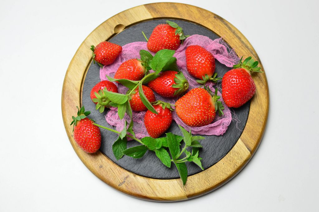 Erdbeeren mit Pfefferminzblättern auf runder Schieferplatte mit Holzrahmen und rosa Netz