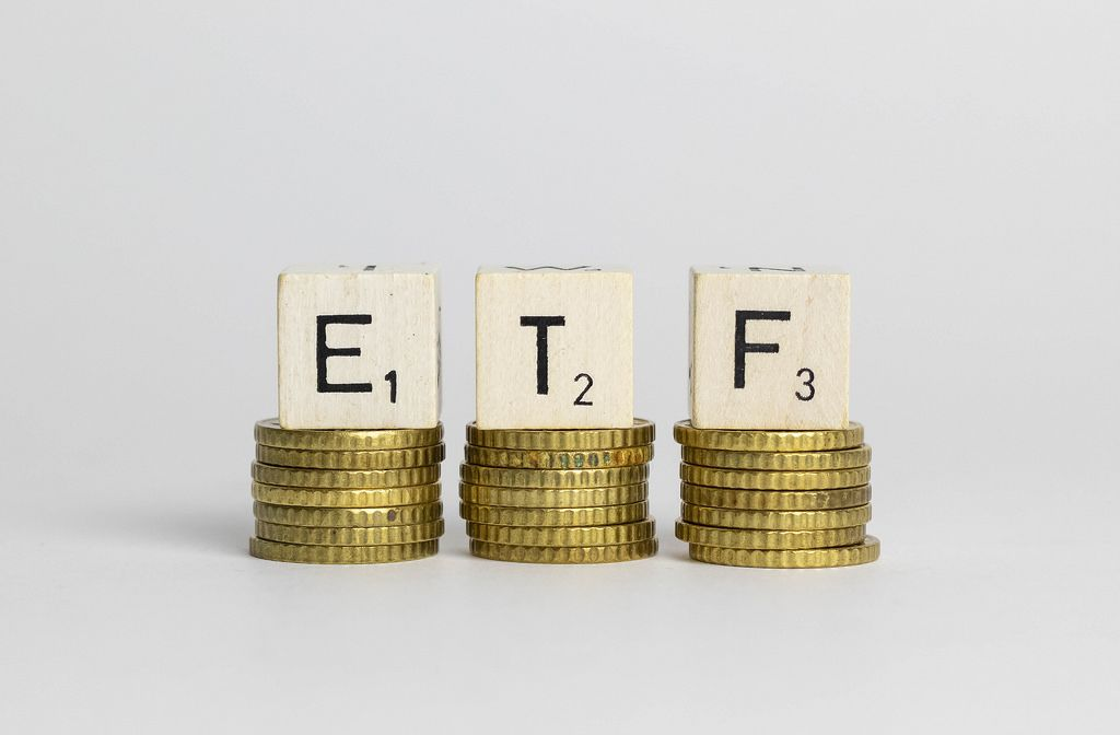 ETF exchange traded fund on the stacks of golden coins