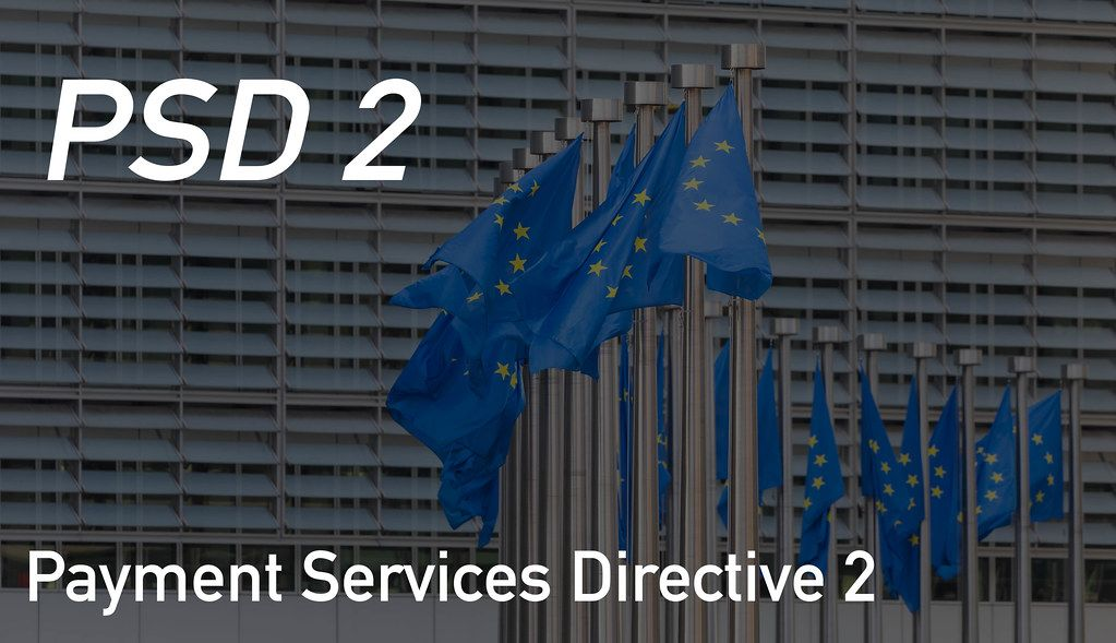 EU flags waving in front of European Parliament building with Payment Services Directive 2 text