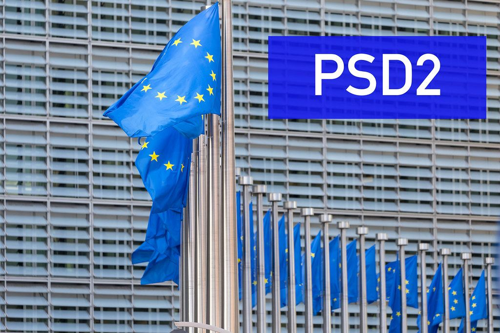 EU flags waving in front of European Parliament building with PSD2 text