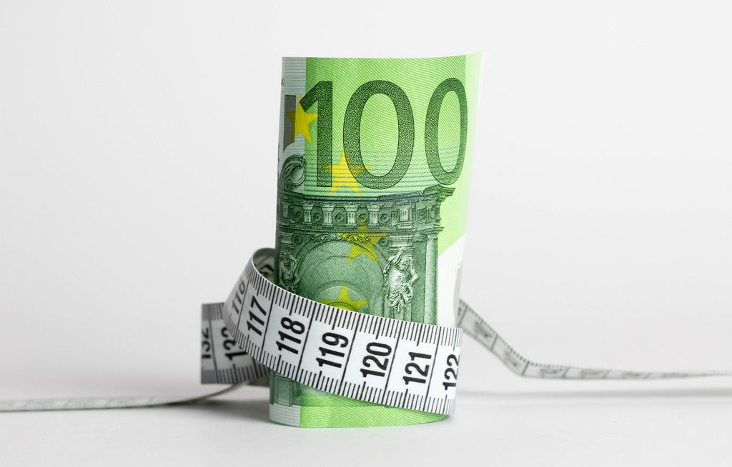 Euro banknote with measure tape on white background