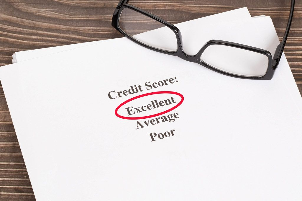 Excellent Credit Score result with glasses on wooden table