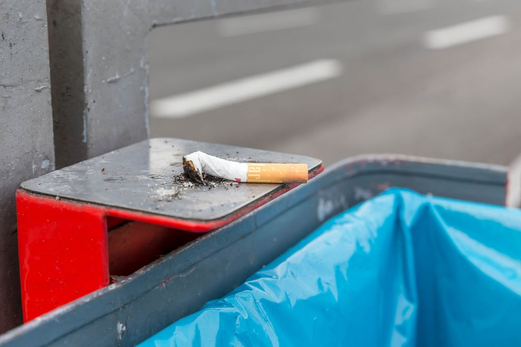 Expressed Marlboro cigarette spring lies on metal holder of a trash bin