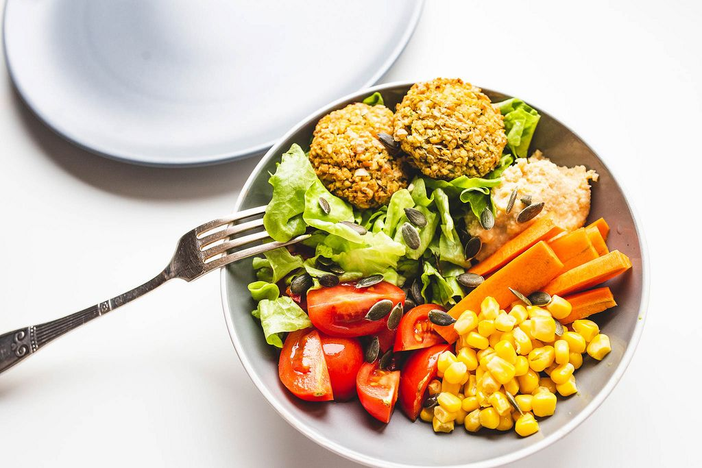 Falafel, hummus and vegetables buddha bowl with plate and fork