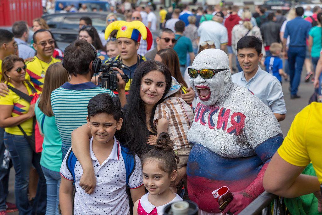Familie fotografiert sich mit einem über den ganzen Körper bemalten russischen Fußball-Fan