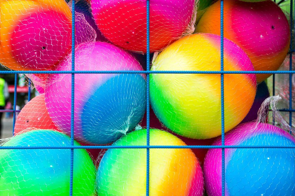 Farbige Gummibälle hinter einem Gitter