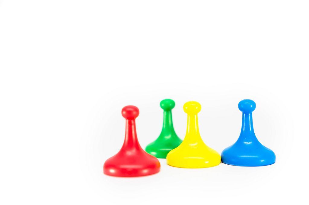 Farbige Spielfiguren in rot, grün, gelb und blau vor weißem Hintergrund