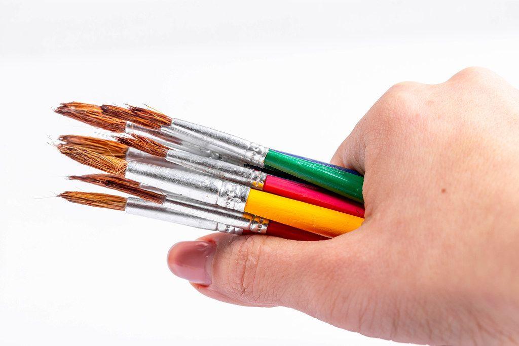 Farbpinsel in einer Frauenhand vor weißem Hintergrund
