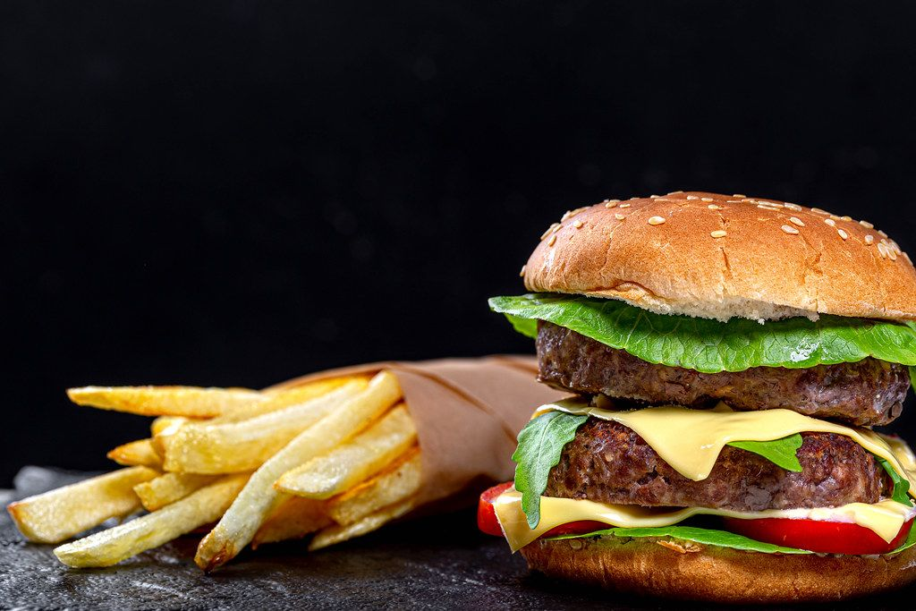 Fast food concept-French fries and hamburger on black background