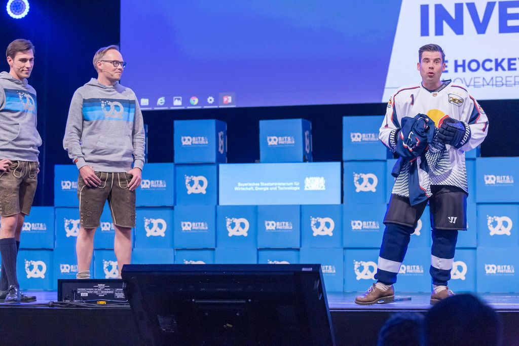 Felix Haas in Eishockey Outfit auf der Bühne, mit Bruckschlögl und Dr. Bernd Storm van's Gravesande
