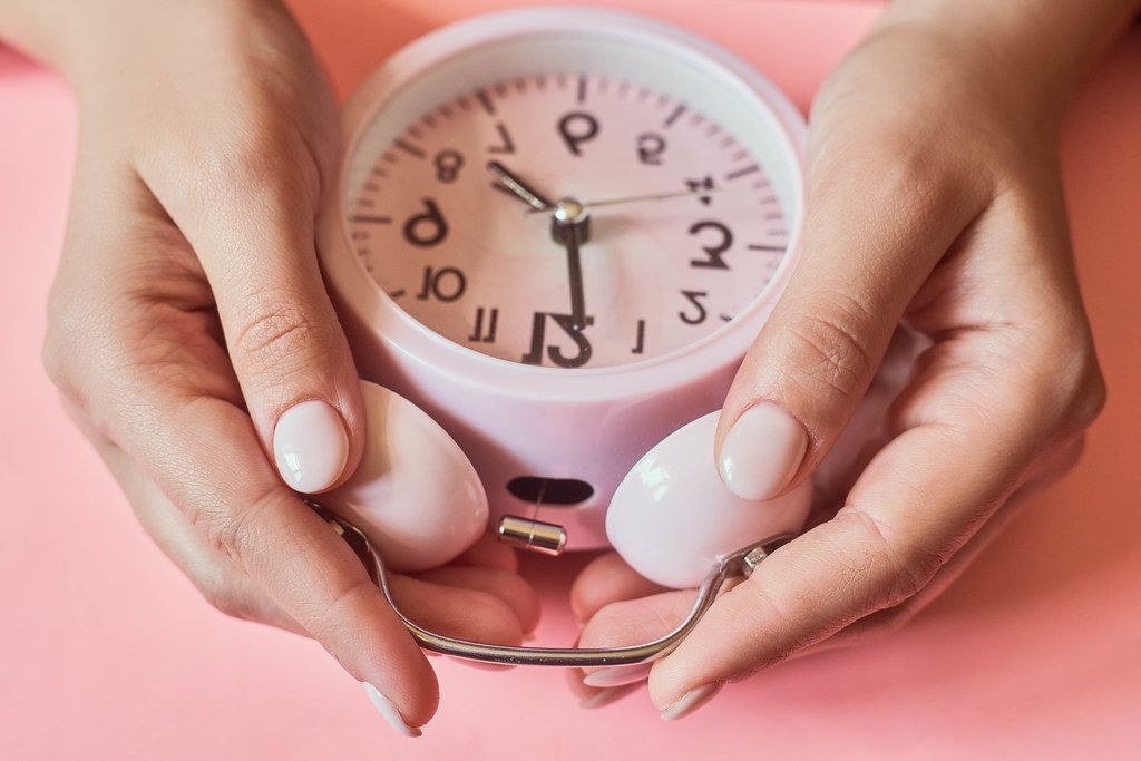 Female checking a time. Woman hands taking an alarm clock (Flip 2020)