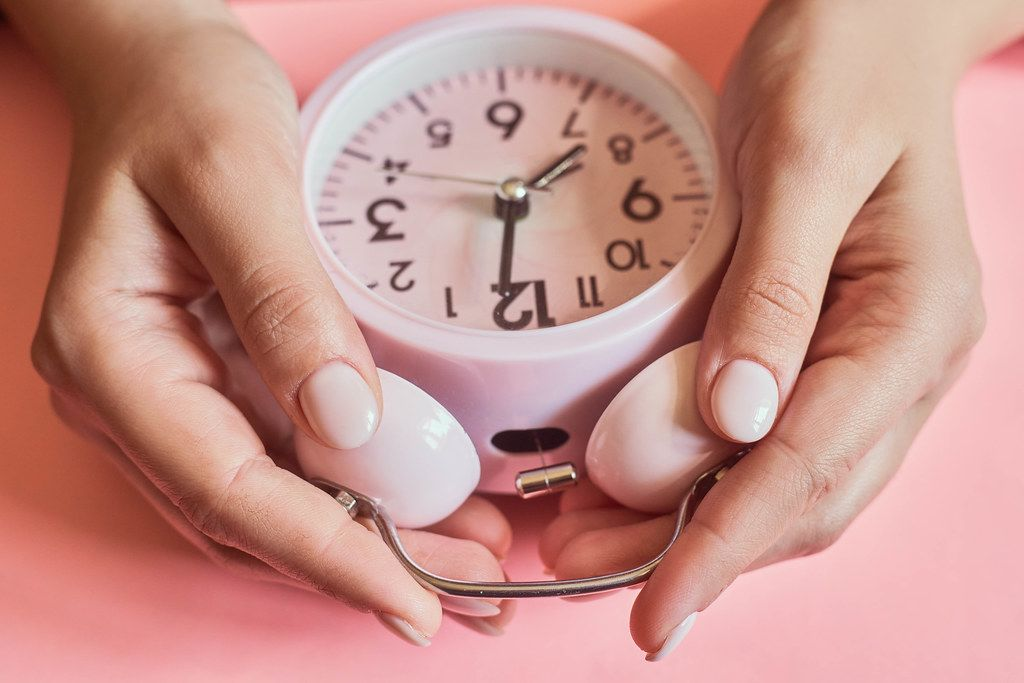 Female checking a time. Woman hands taking an alarm clock.jpg