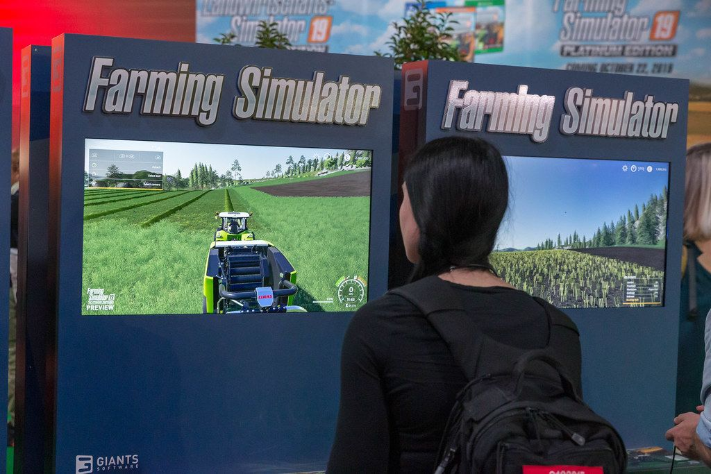 Female games fair visitor plays Farming Simulator by GIANTS Software at Gamescom