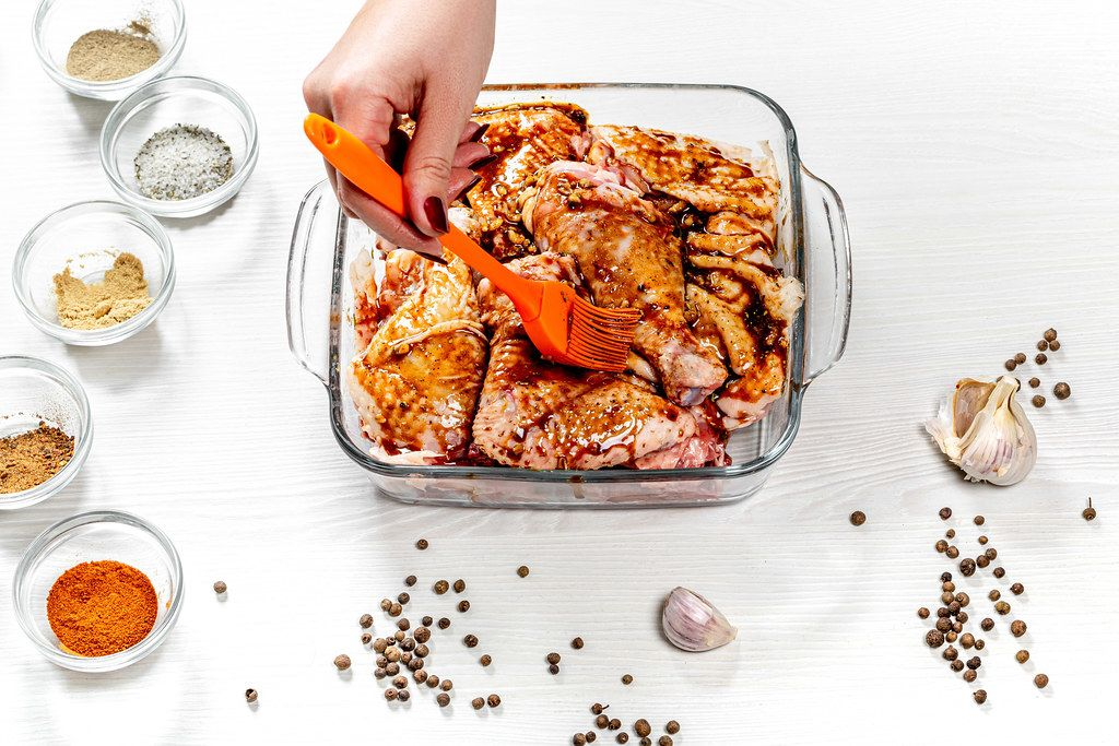 Female hand spreads pieces of chicken marinade. Top view