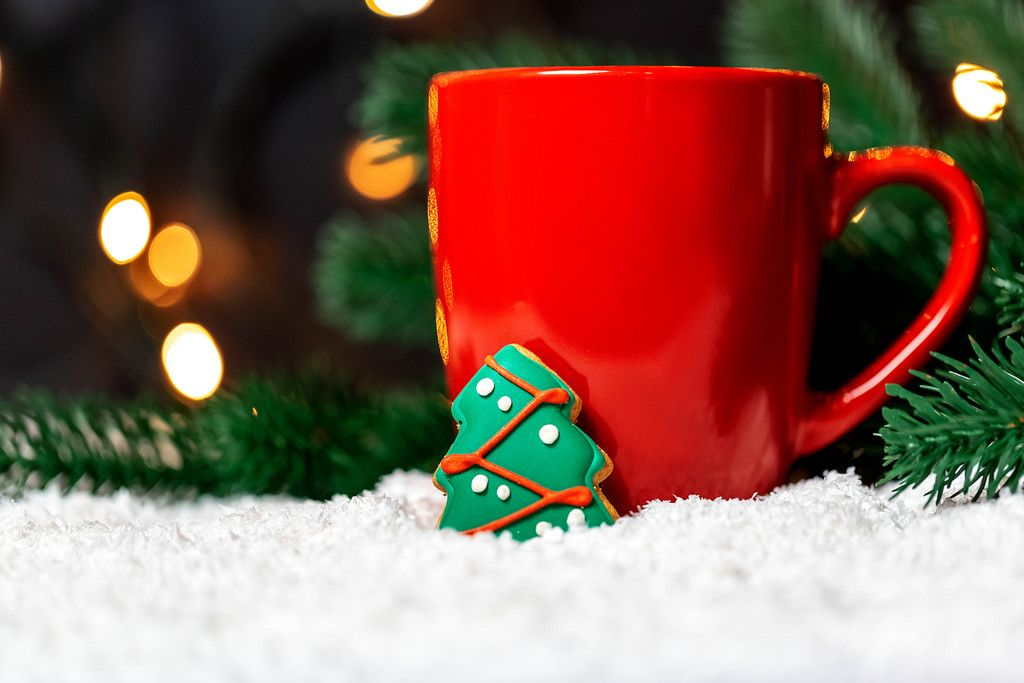 Festive background with a Cup of Tea and gingerbread tree on a snow background