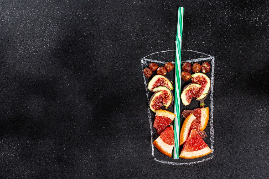 Figs, grapefruit and hazelnuts for blending smoothie in painted glass on black chalkboard. Top view. Healthy eating concept