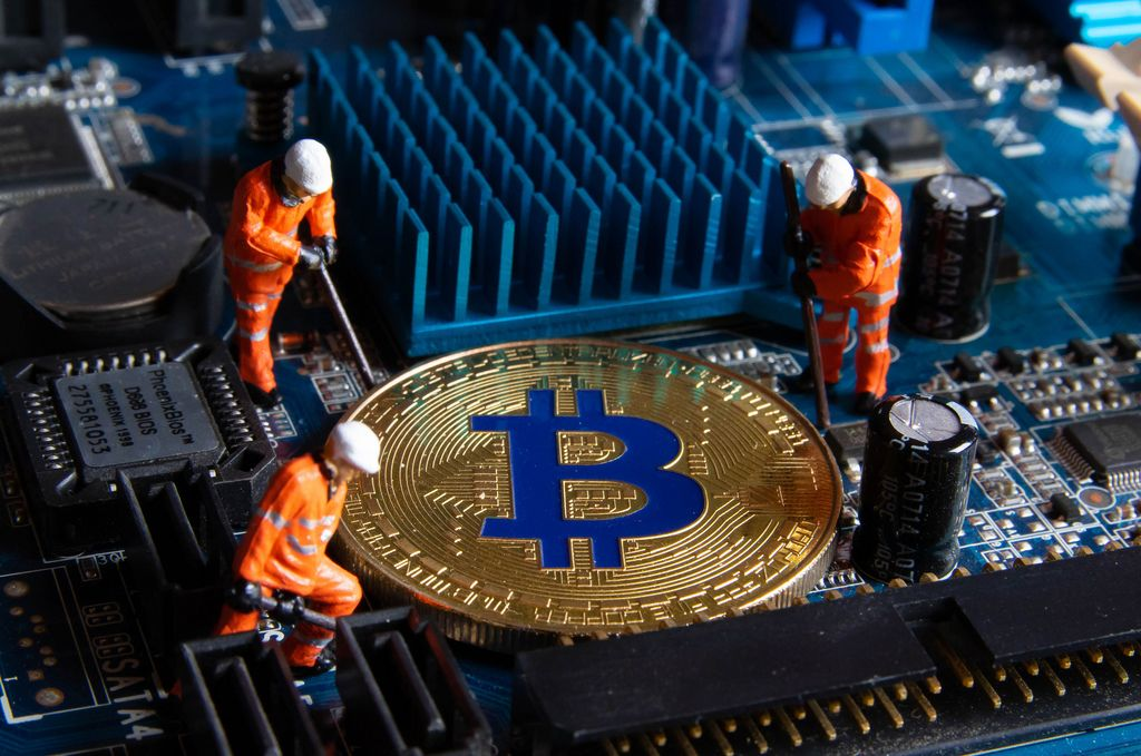 Figures working on a golden Bitcoin