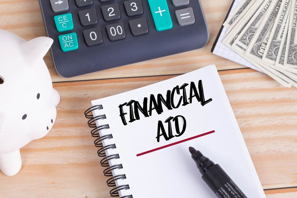 Financial Aid text in notebook with piggy bank and calculator on wooden table