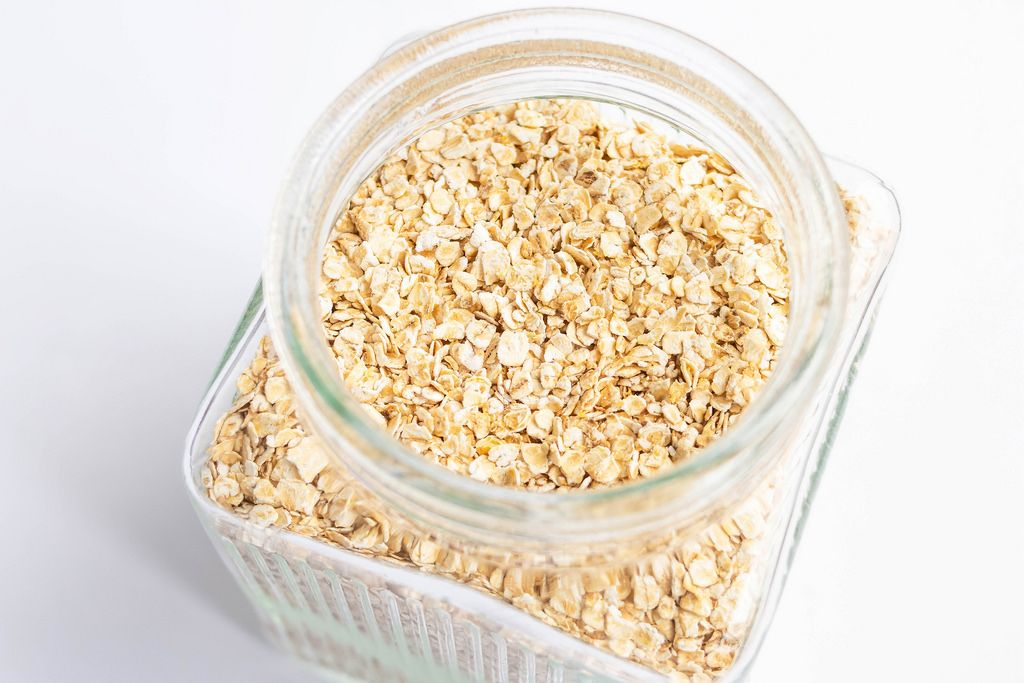 Fine oats in a glass jar on white background